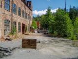 En nedlagd fabrik i tegel med trasiga fönster. Foto.