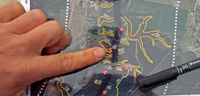 Finger som pekar på karta med markeringar i olika färger.